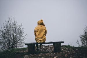 Woman sitting alone in raincoat. This is symbolic of the isolation one might feel from feeling disconnected from their partner. Journey to New Beginnings offers intimacy counseling in Madison, AL. Contact us for sexual intimacy therapy, sex therapy online, and more.