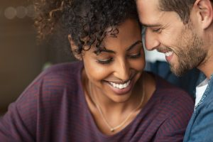 A couple hold each other close as they smile. Their relationship has never felt stronger after intimacy counseling in Madison, AL. Journey to New Beginnings offers sexual intimacy therapy in Madison, AL, sex and intimacy therapy, and more.