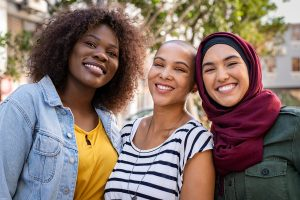 Three multiethnic friends smile at the camera. One of the friends is feeling more confident about overcoming her trauma after talking to a sexual abuse therapist in Madison, AL. Journey to New Beginnings offers sexual abuse therapy, trauma counseling, and more.