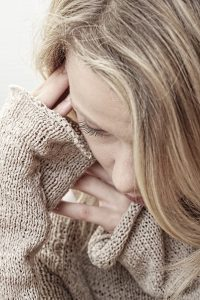 Close up of woman looking down with her hands next to her face. She's been talking to a sexual abuse therapist in Madison, AL in order to overcome past trauma. Journey to New Beginnings offers online sexual abuse therapy, trauma counseling, and more. Contact a sexual abuse therapist for support in healing sexual trauma.