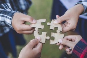 Four hands hold wooden puzzle pieces close together. This symbolizes the benefits of working with a sexual abuse support group in Madison, AL. We offer group therapy in Madison, AL. Join our domestic violence support group or learn about intimacy counseling in Huntsville, AL today.