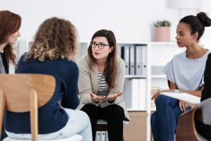 Woman gestures as she talks to the group sitting around her in a circle of chairs. This symbolizes what a group therapy session may look like. A therapy support group in Madison, AL can offer support through group therapy.