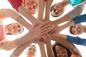 Women in a circle with hands in the middle like a team, all looking through their arms to the camera and smiling. This symbolizes what a group therapy session may look like. A therapy support group in Madison, AL can offer support through group therapy.