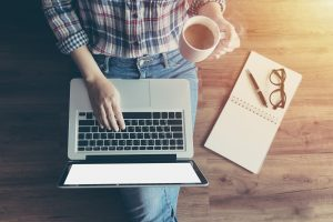 Top down of an individual holding a cup of coffee in one hand while typing on their laptop with the other. This could symbolize someone getting ready to meet with an online therapist from home. We offer online therapy in Madison, AL, teletherapy, and other services! Contact us today to get in touch with an online therapist.