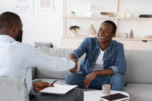 A man shakes the hand of the person sitting across from them. This could represent a clinical supervisor greeting their client. Contact a licensed clinical supervisor for more info on how clinical supervision in Madison, AL can help.